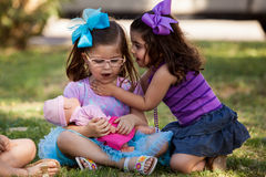 Let me tell you a secret. Pretty little girl telling her friend a secret while hanging out at a park Stock Photography