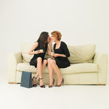 Let me tell you a secret. Two young beautiful women sitting on sofa, drinking coffee and whispering secrets at shopping. copy space available Royalty Free Stock Photo