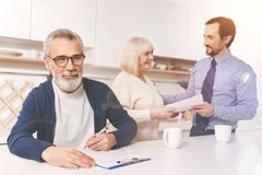 Positive aged man signing papers. Let me think. Pleasant retired men signing papers while his wife and real estate agent standing in the background while talking Royalty Free Stock Image