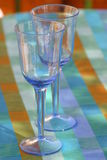 Let the party begin. Two empty glasses, silence before the guests arrive. Soon the party begins, and the glasses will be filled with white wine.It is summer in Royalty Free Stock Photos