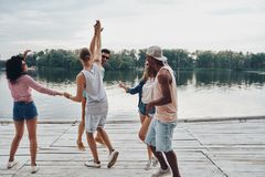 Let the party begin!. Full length of young people in casual wear smiling and gesturing while enjoying beach party royalty free stock photography