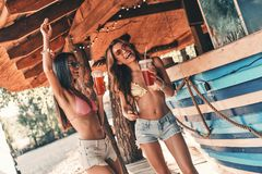 Let the party begin!. Two attractive young women smiling and enjoying cocktails while dancing near the bar counter royalty free stock image