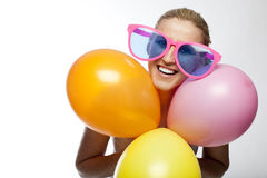 Let the party start. Beautiful laughing young woman in outsized coloured glasses holds a bunch of colourful party balloons isolated on white with coyspace Royalty Free Stock Photos