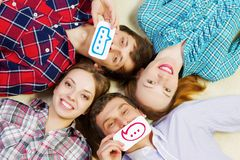 Let's be friends. Group of young smiling people lying on floor in circle with phone symbols royalty free stock image