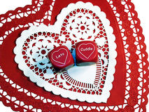 Let's Cuddle 2. Romantic dice that say Let's Cuddle on red and white paper hearts.  White background Royalty Free Stock Photos