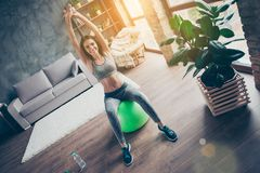 Let`s do it! Portrait of active enduring flexible charming beaut. Iful cute muscular wearing tight fashionable sportive clothes putting hands up sitting on light Royalty Free Stock Image