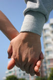 Let's Do This Together. A couple holding hands, with apartments in the background Stock Photo