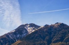 Let's fly. Trace of the airplane in blue sky coming to changed weather. all above mountains of switzerland, ticino Royalty Free Stock Photo