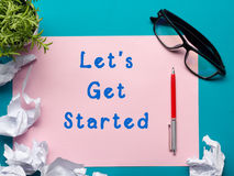 Let's get started message - Office desk table with supplies top view.  crumled paper, pen, glasses and flower. Royalty Free Stock Image