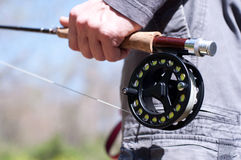 Let's go fishing!. A man holding a fly fishing rod and reel Stock Images