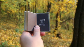 Let`s go journey explore trip traveling destination adventure idea. autumn wood on a background. Hand holding a book with the inscription on the background of stock video footage