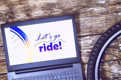 Let`s go ride. Part of the bicycle wheel. laptop on old wooden background royalty free stock photo