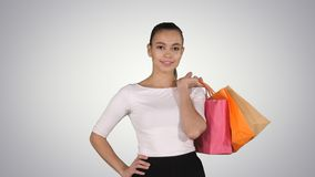 Let`s go shopping! Woman walking with shopping bags on gradient background. royalty free stock photo