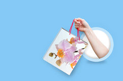 Let`s go spring shopping. Hand holding paper bag . Let`s go spring shopping Stock Photo