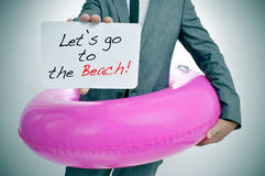 Let's go to the beach. Businessman with a pink swim ring showing a signboard with the text let's go to the beach written in it Royalty Free Stock Photos