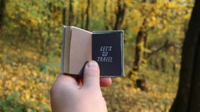 Let's Go Travel Journey Adventure Traveling Exploration idea. Autumn wood on a background. Hand holding a book with the inscription on the background of autumn stock video footage