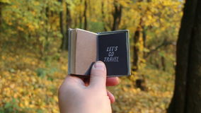 Let`s Go Travel Journey Adventure Traveling Exploration idea. Autumn wood on a background. Hand holding a book with the inscription on the background of autumn stock video footage