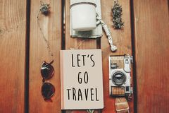 Let`s go travel text on notebook, wanderlust concept. map with s. Unglasses, photo camera, mug, notebook on wooden background, top view. stylish traveler hipster Stock Photography