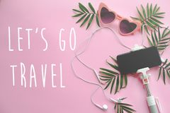 Let`s go Travel text on stylish pink sunglasses, phone on selfie. Stick, headphones, and green palm leaves on pink background. summer vacation flat lay. time to Stock Photography
