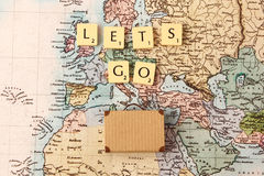 Let's go travel the world. Vacation concept with suitcase and map Royalty Free Stock Images