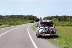 Let's go on a trip! The car is by the road and ready to trip. Two bicycles mounted on trunk of jeep. Summer day. Empty place for message. Copy space. Travel ( Royalty Free Stock Photography