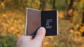 Let`s go wild. Text and book. Hand holding a book with text stock video footage