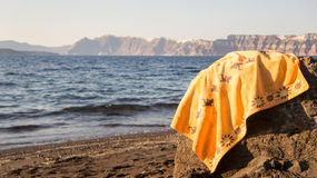 Let's have a bath!. Beach towel on a rock while the swimmers are having a bath in a Santorini beach, Greece (Europe Royalty Free Stock Image