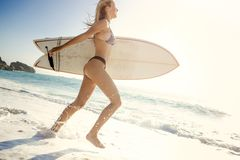 Let`s hit the waves. Beauitful young surfer girl running to the waves with her surfboard Royalty Free Stock Photography