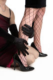 Let's hold on. Woman wearing black gloves holding fishnet covered legs Stock Photo