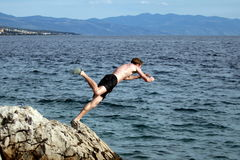 Let's Jump. A young man jumps from a cliff into the sea Stock Image