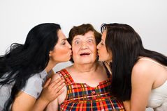 Let's kiss  grandma!. Surprised grandmother face being kissed by her two granddaughters,check also  Grandmother Stock Image
