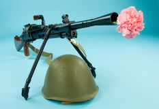 Let's Make Love, Not War!. Machine gun with pink in a barrel and helmet royalty free stock image