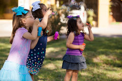 Let's make some bubbles. Beautiful Hispanic cousins playing with bubbles outdoors at a park Stock Images