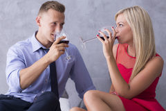 Let's make a toast. Man and the women sitting close each other and drinking wine Royalty Free Stock Image