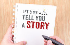 Let`s me tell you a story work on white ring binder notebook wit. H hand holding pencil on wood table,Business concept Royalty Free Stock Photo
