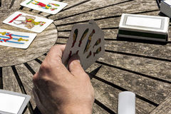 Let`s play cards outdoor in a wooden table. Friends ready to play cards outdoor in a wooden table Stock Photography