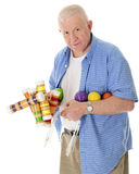 Let's Play Croquet. A casual senior adult man looking at the viewer carrying a load of croquet mallets, balls and wickets.  On a white background Royalty Free Stock Images