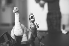 Black and White Image of a Brontosaurus and T-Rex-Toys. Black and white image of dinosaur toys in a child's playroom with the child in the background blur Royalty Free Stock Images