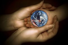 Let´s protect Earth. Child´s and woman´s hands in tender gesture with our planet Earth like a concept for ecology, environment and love for the world Royalty Free Stock Photo