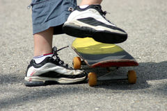 Let's roll. 'Closeup of boy's feet and legs about to take off on a skateboard Royalty Free Stock Images