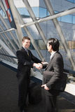 Let's Shake on It. Two businessmen smiling and shaking hands in an office lobby Stock Photo