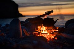 Let's sit down and talk?. Photo of boiling the kettle over the fire at sunset Stock Photos