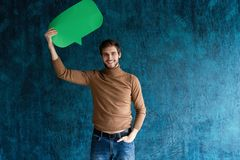Let`s start a conversation. I speak the language of success. Handsome young man holding up speech bubble  on stock photo
