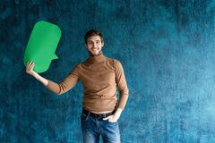 Let`s start a conversation. I speak the language of success. Handsome young man holding up speech bubble  on stock image