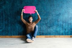 Let`s start a conversation. I speak the language of success. Handsome young man holding up speech bubble  on stock photography