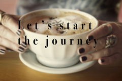 Let`s start the journey quote on coffee. Inspirational quote Lets start the journey on a picture with two hands holding a good bowl of coffee to start the day royalty free stock photos