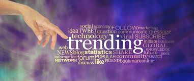 Let`s take a look at what`s trending concept word cloud. Female hand point a finger at the word TRENDING surrounded by a word cloud against a modern purple royalty free stock photo