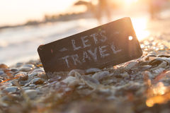 Let's Travel concept. Lets go travel, adventure motivation concept. Sign with the text Let's Travel on the beach, sunset Royalty Free Stock Image