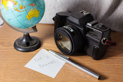 Let s travel. Old camera with globe and stationary Stock Photography