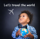 Let's travel the world. Portrait of little African schoolboy holding in hands small globe, dreaming about traveling all over the world, happy childhood concept Royalty Free Stock Photography